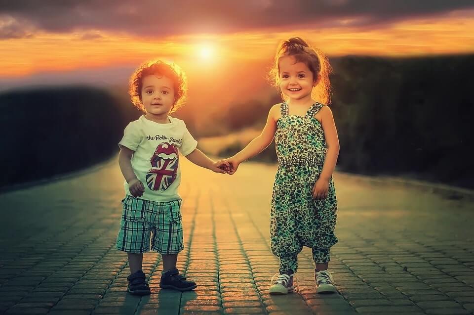 dzieci chłopczyk i dziewczynka trzymają się za ręce