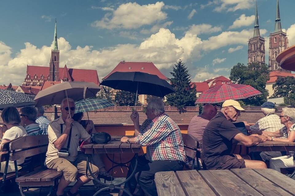 grupa osób starszych siedzących pod parasolami