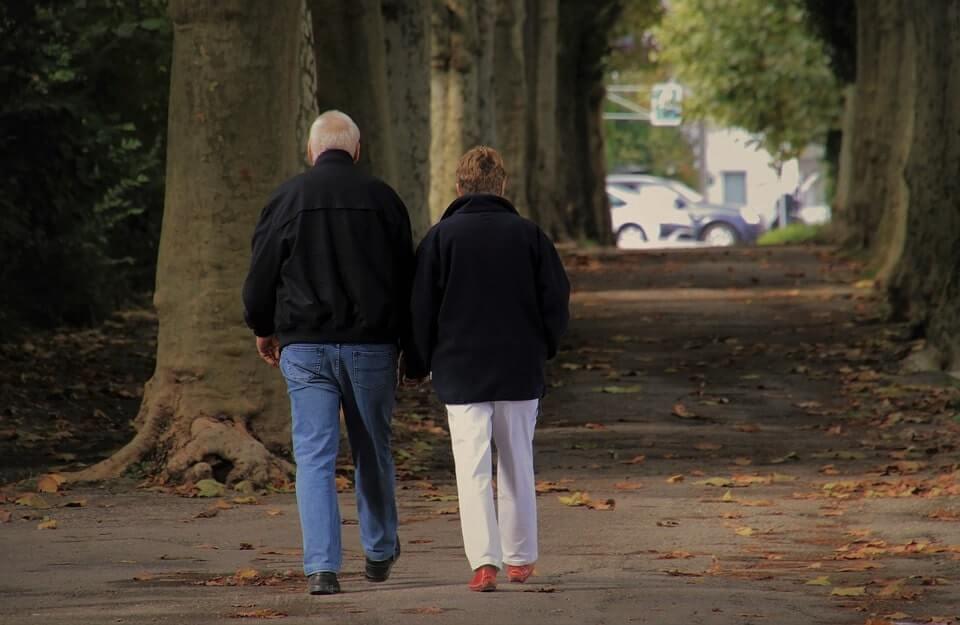 dwójka emerytów, spacerujących w parku