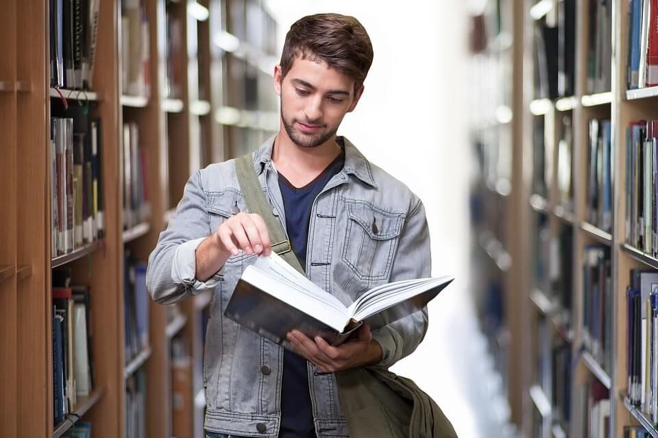 facet czytający książkę w bibliotece